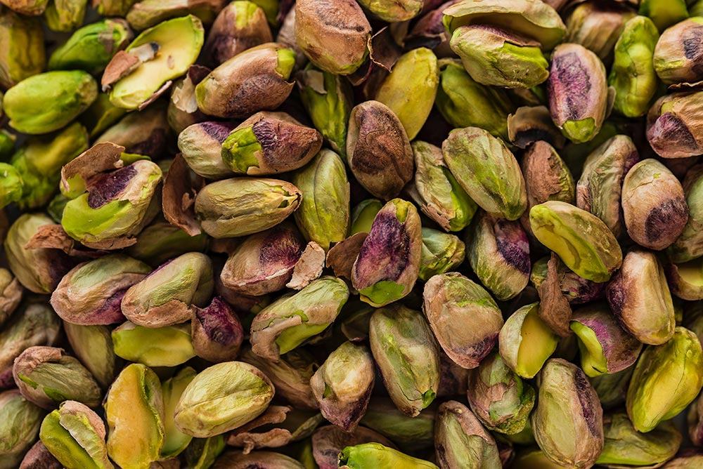 The incredible health benefits of eating nuts. A huge pile of pistachio nuts