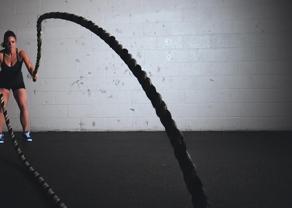 The three pronged attack to burn belly fat. A women uses ropes to exercise in a gym