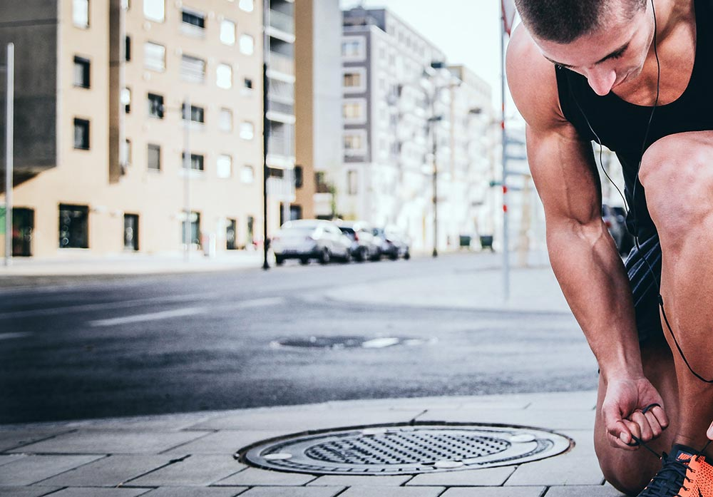 Creatine how and when to use it. A runner bends down to tie his shoe lace in the street