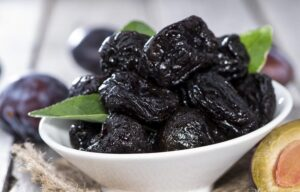 Eat prunes to build muscle and ease workout soreness. Prunes in a bowl on a kitchen side.