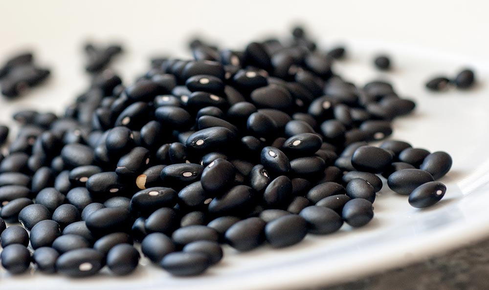 Eat black beans for an endurance booster. Black beans on a table top side