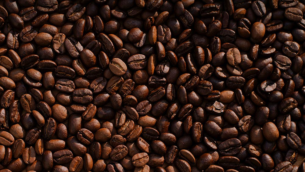 Health benefits of drinking coffee. Coffee beans sit piled up