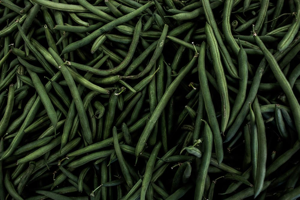 The benefits of eating Green beans and Fava beans. lots of green beans piled up together.