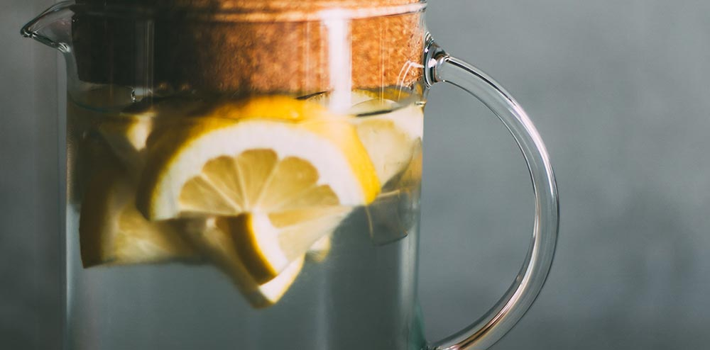 15 health benefits of lemon water. Lemon water sitting in a jug