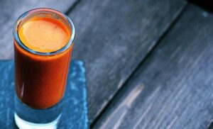 Flush out toxins with this strong detox shot. An orange shot of fruit and vegetables sits on the side of a table