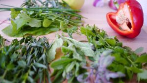 8 health boosting herbs and what they do for you/ A pepper and a variety of mixed herbs lay on a kitchen table.