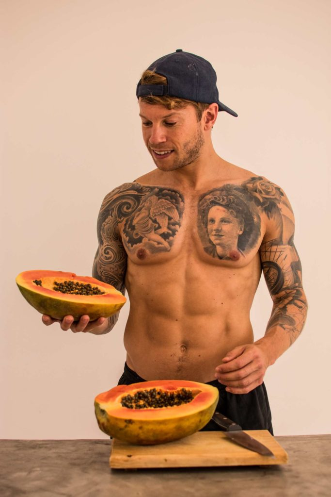 The benefits of eating Papaya. A man holds a papaya cut in half