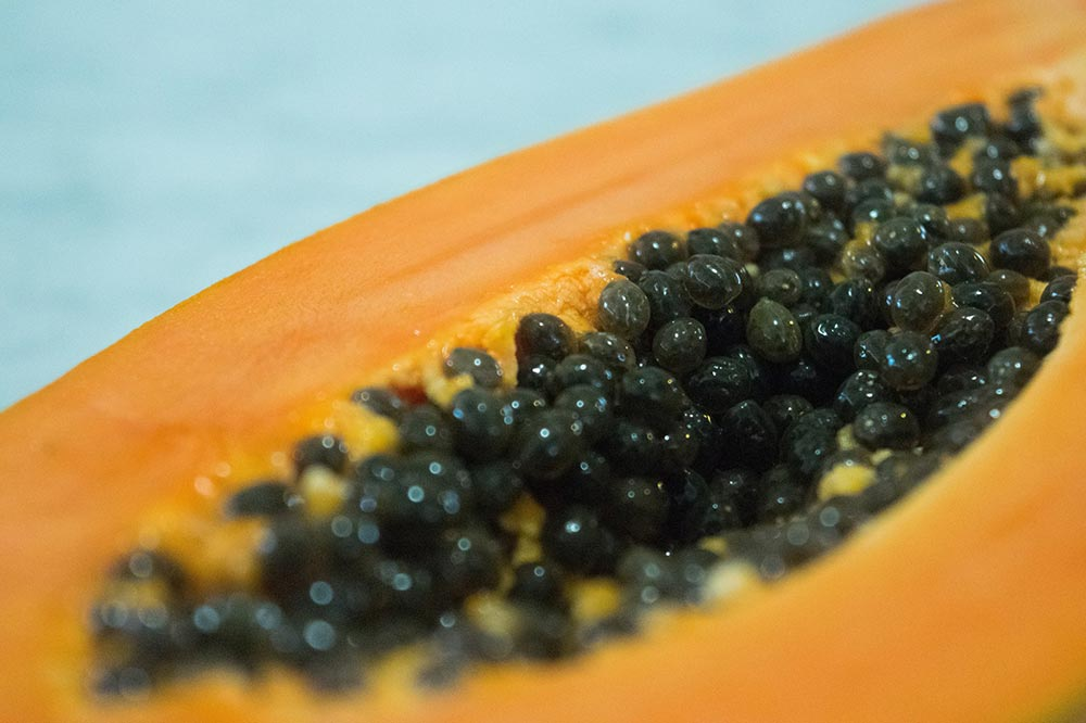 The benefits of eating Papaya. A papaya cut in half showing it's seeds