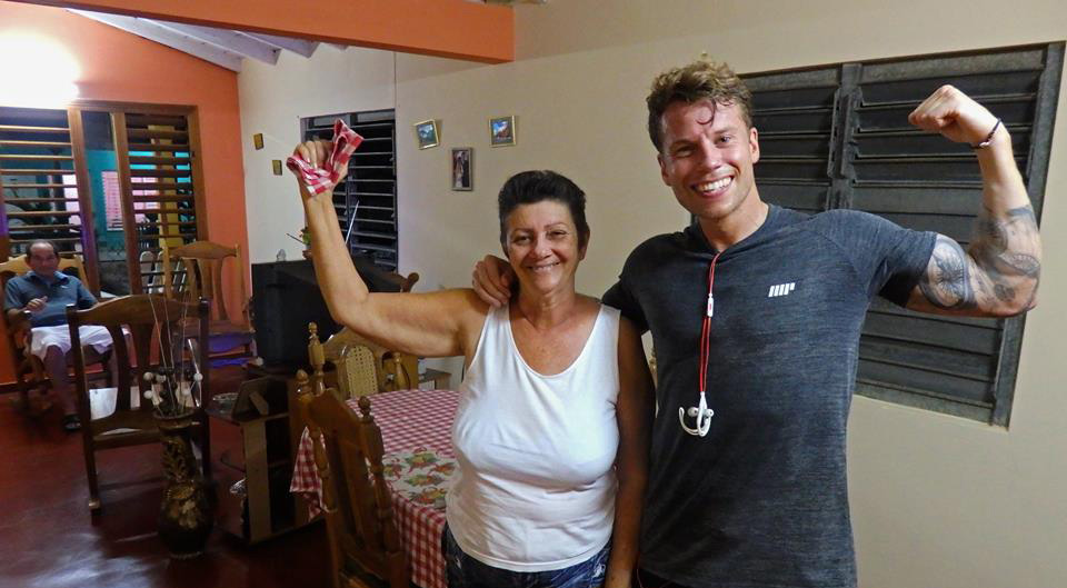 How to travel, keep fit and workout. Man flexes his biceps hugging an oder Cuban women