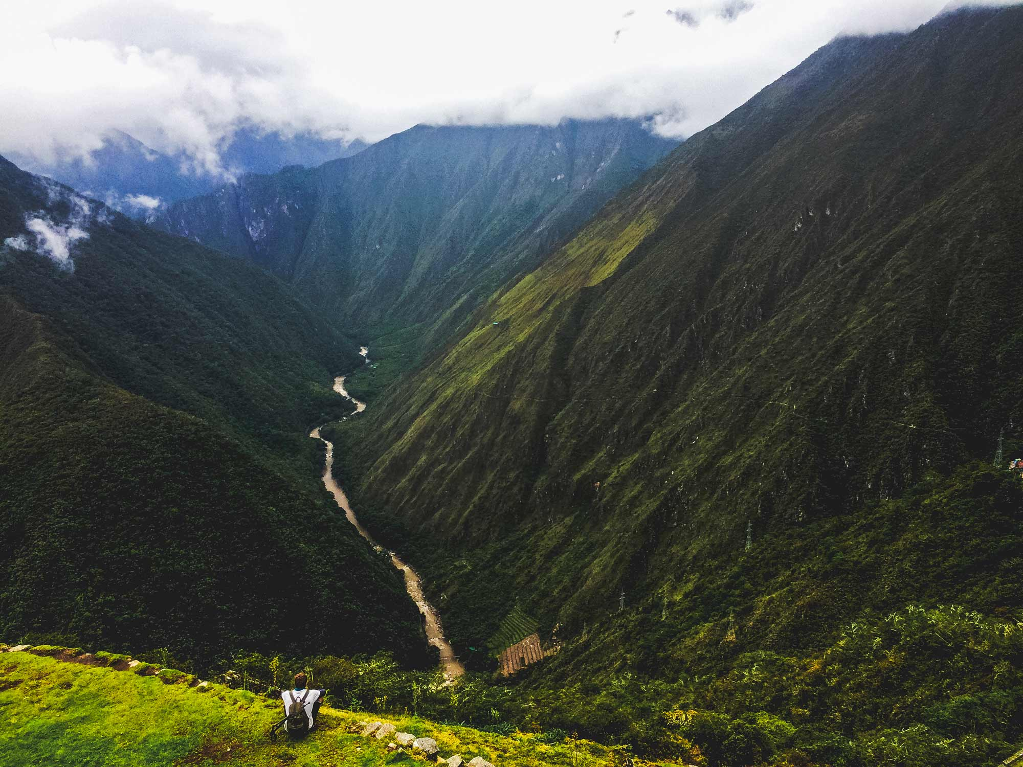 Trekking the Inca Trail to Machu Pichu. TRX Traveller Adam Atkinson sitting on a cliff edge looking over a river and the Andes mountain on day 4 of the Inca Trail trek