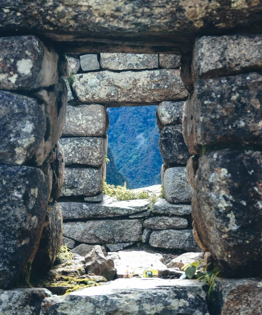 Trekking the Inca Trail to Machu Pichu. Looking through two stone windows in the city of Machu Pichu out onto The Andes