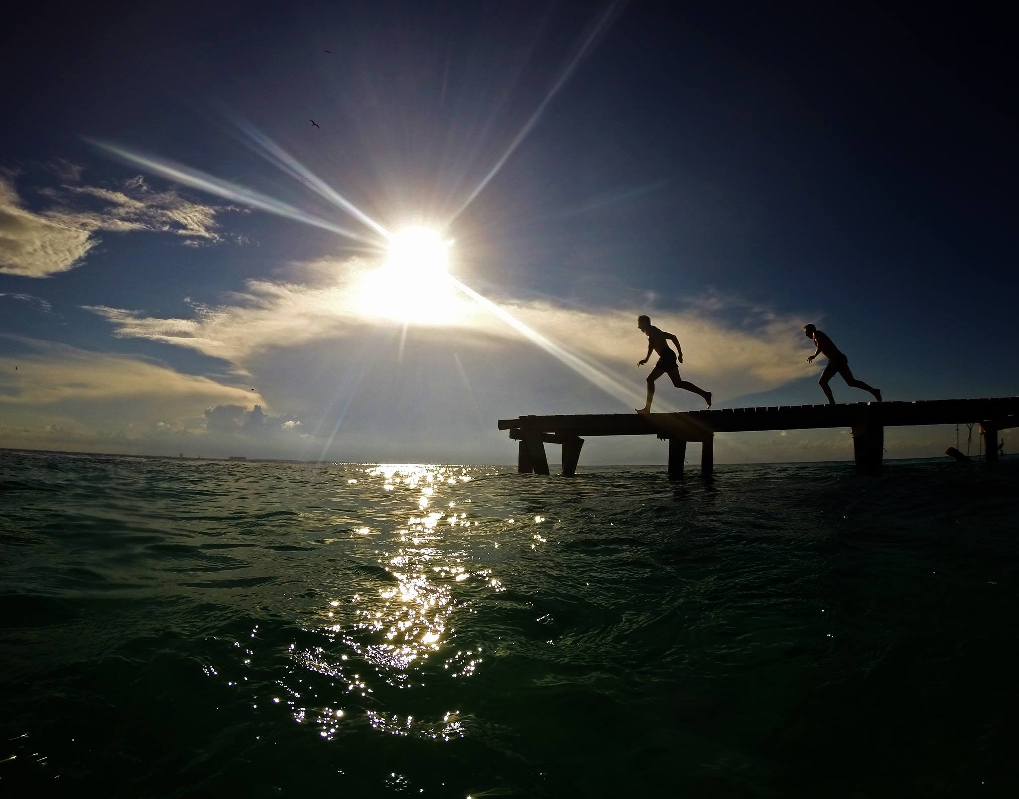 Is it worth backpacking Isla Mujeres? Two men run along a jetty ready to jump in the water