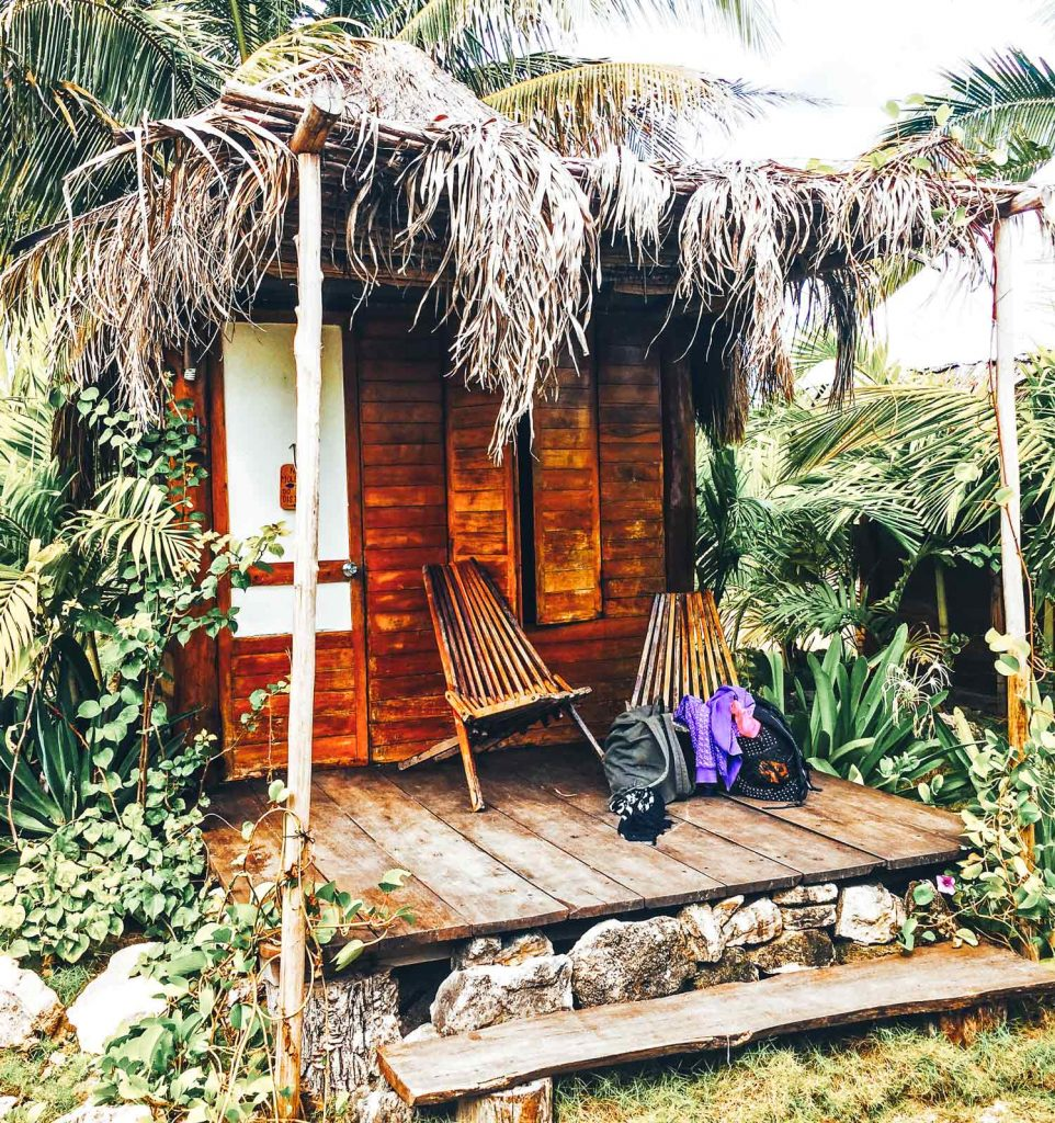 Pro's and cons of travelling the Mahahual Coast. A little wooden hostel beach hut situated on the coastline amongst palm trees