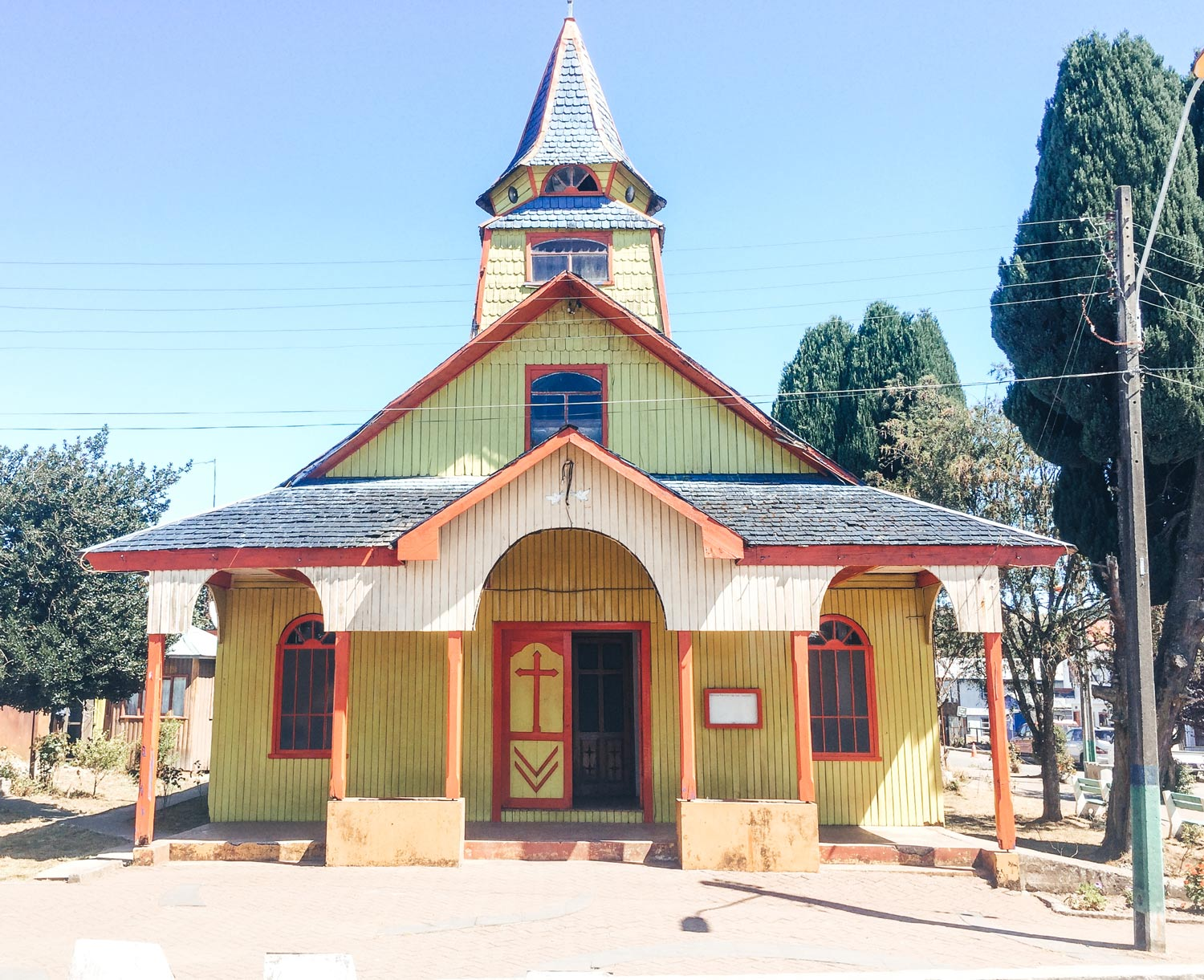 Here's the best way to backpack Chiloé Island. A green church made from wood with a large spire