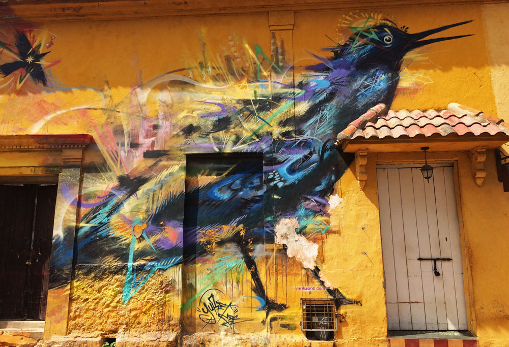 A backpacking guide to Cartagena. A graffiti bird on a bright yellow wall in old town.