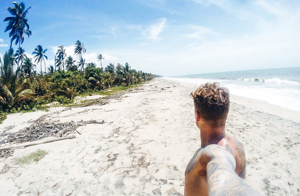 Why Palomino is a must see backpacking destination. The far right of the beach after a 30 min walk. A man stands with his back to camera looking up the miles of golden sands at Palomino