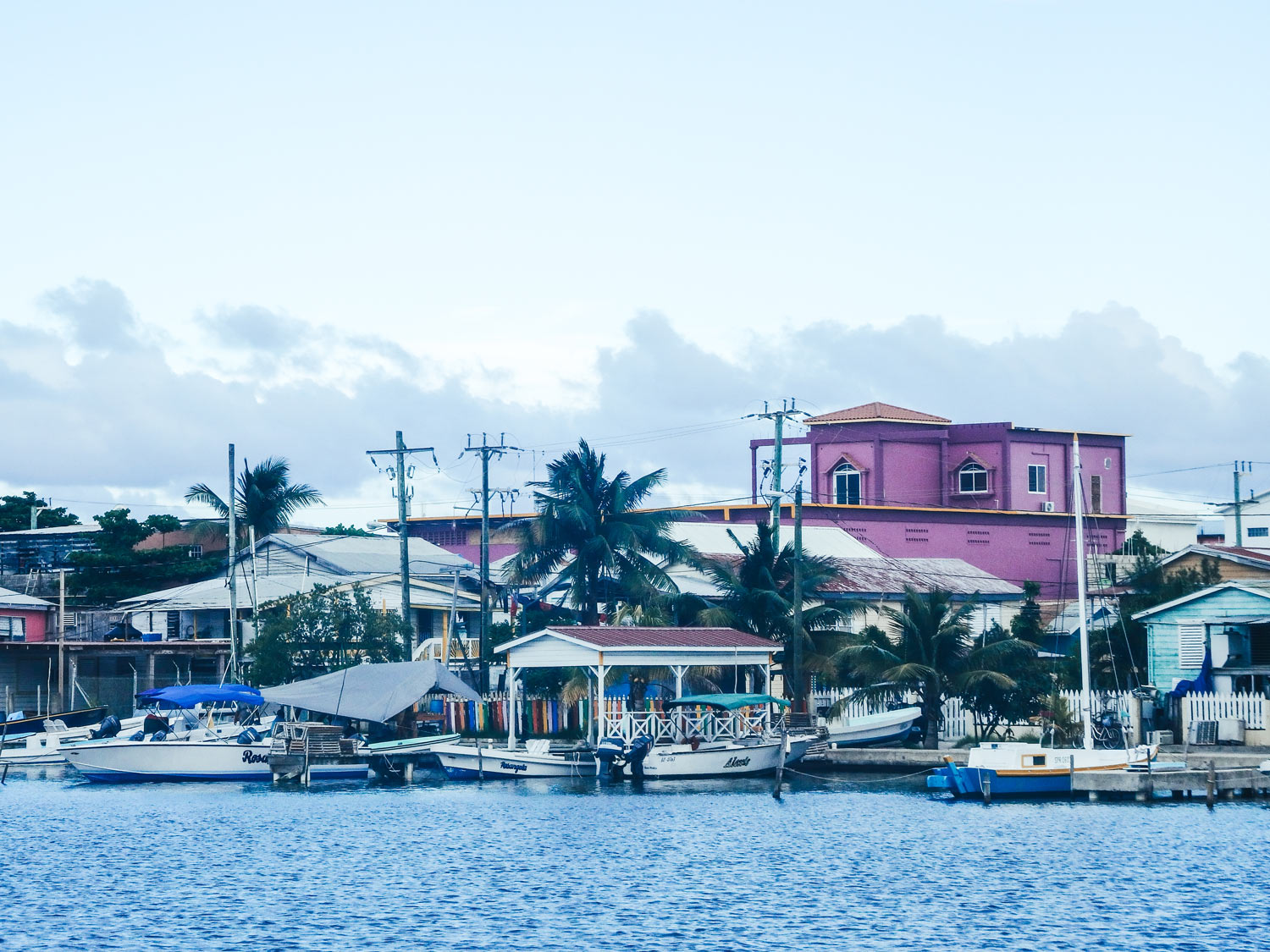 Travelling Caye Caulker the tropical paradise. A view of a pink building on the island water whilst arriving from the boat