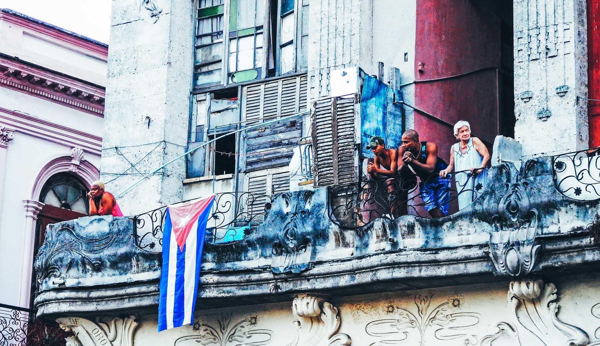 Here's why you'll feel at home backpacking Havana. People stand on a balcony looking out in Havana