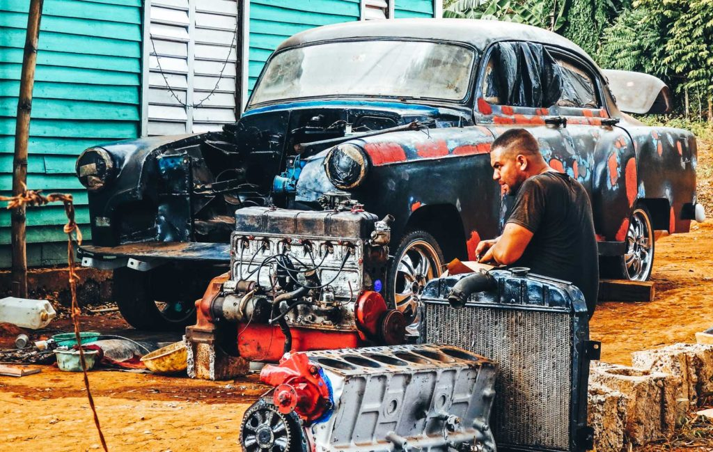 One awesome reason to backpack Vinales. A Cuban man fixes his car in the front garden