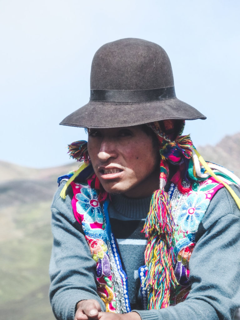 Rainbow Mountain the greatest one day trek on earth. A local Peruvian man wearing a hat stares into camera