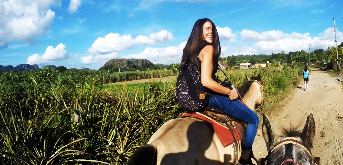 One awesome reason to backpack Vinales. A girl sits on the back of a horse during the gin tour