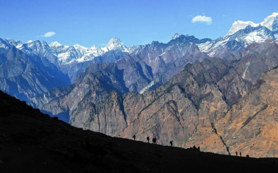The best Himalayan travel adventure on earth: 3 day Kuari Pass Trek. A group of people walk in the shadow of the mountain on day 3 with the Himalayas in the backdrop