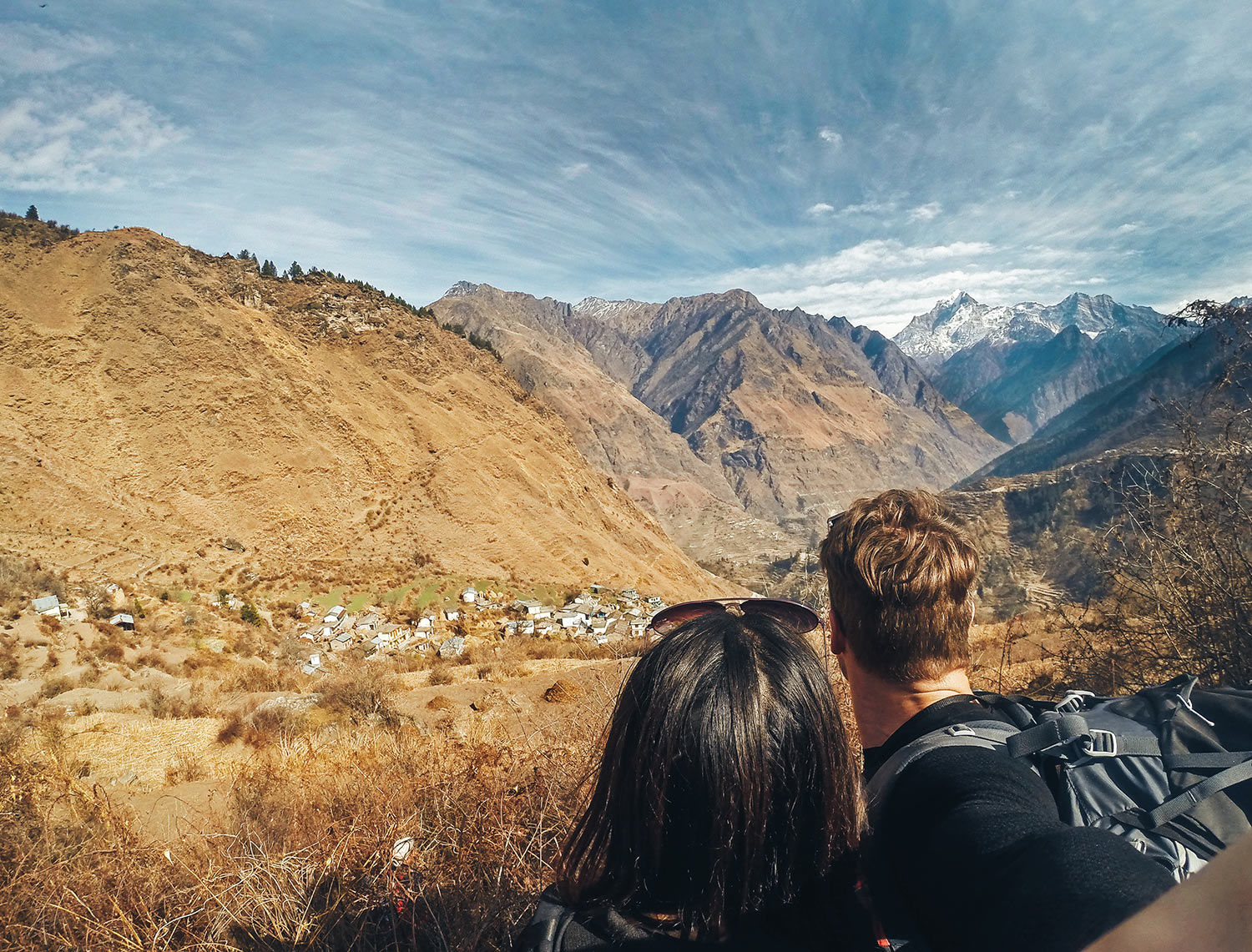 The best Himalayan travel adventure on earth: 3 day Kuari Pass Trek. Two people lookout over the villages of the Himalayas