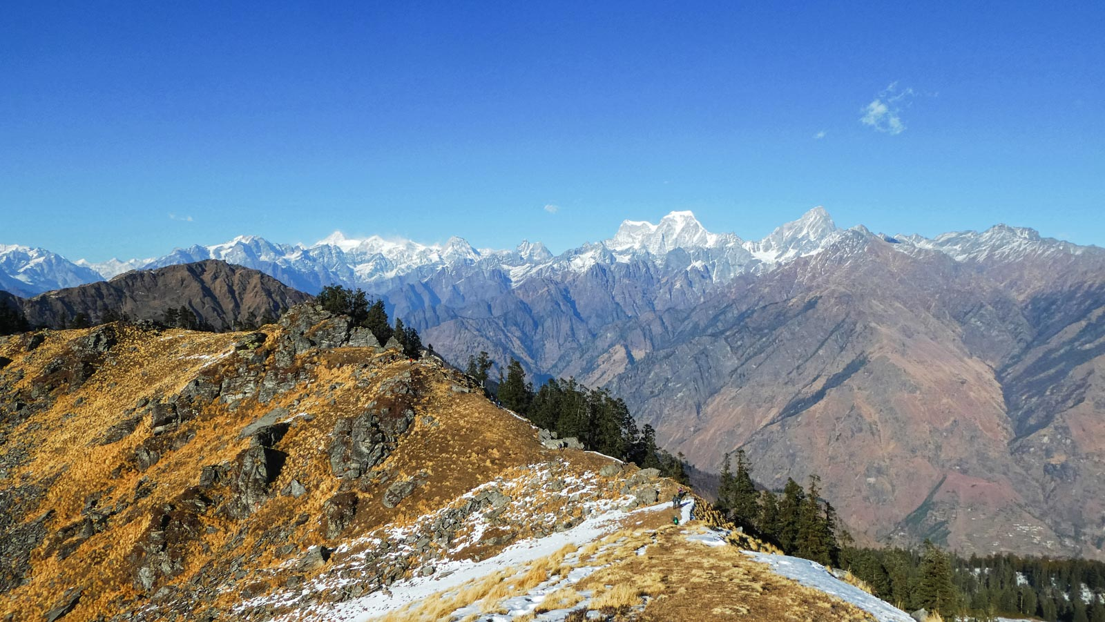 The best Himalayan travel adventure on earth: 3 day Kuari Pass Trek. People walk along the summit of the Himalayan mountains