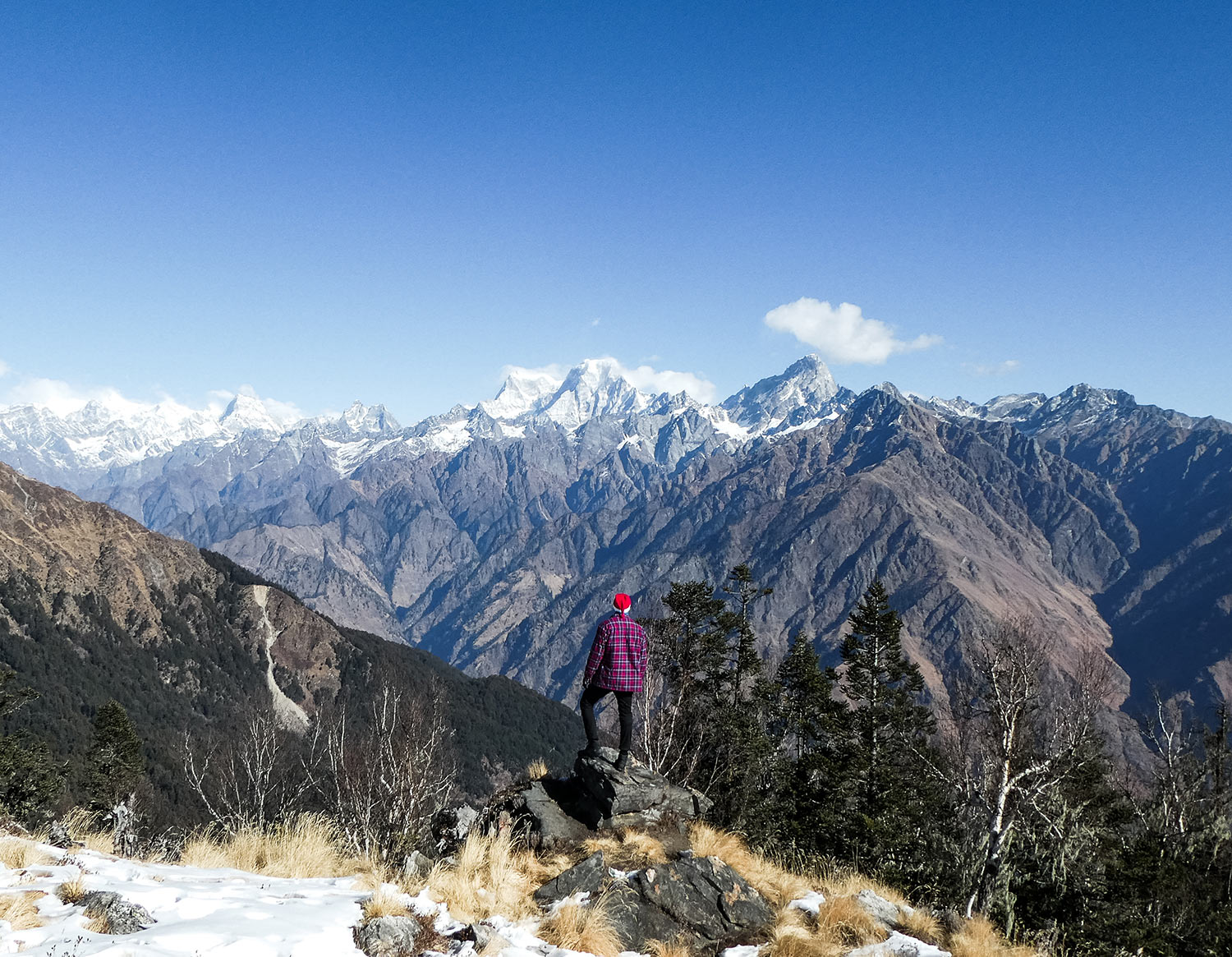 The best Himalayan travel adventure on earth: 3 day Kuari Pass Trek. A man stands at the peak of a mountain with a Santa hat on looking out over the Himalayas