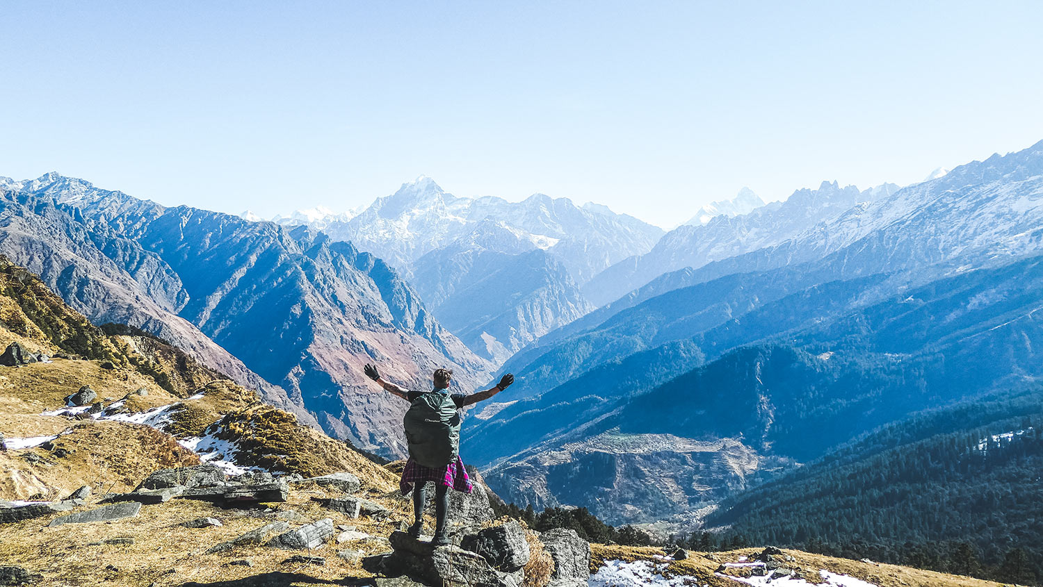 The best Himalayan travel adventure on earth: 3 day Kuari Pass Trek. A man holds his hands out embracing the Himalayan views with mountains in front of him