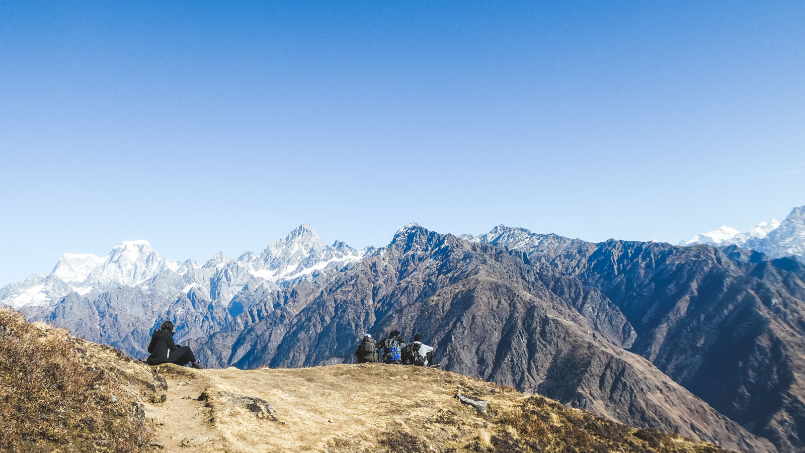 Nutrition and fitness tips for trekking at attitude. Four people sit on top of a mountain in the Himalayas