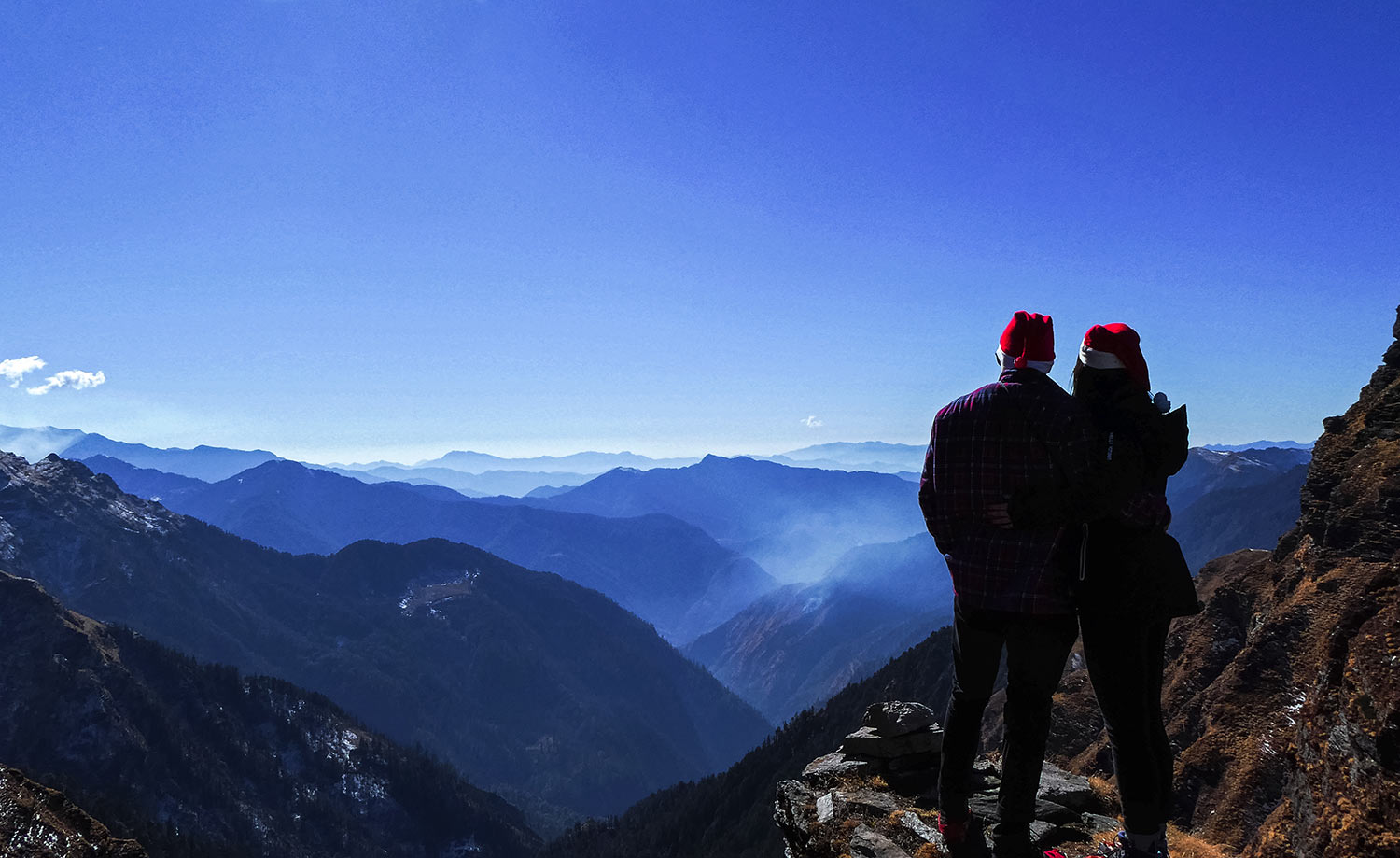 The best Himalayan travel adventure on earth: 3 day Kuari Pass Trek. Two people look out over The Himalayn view from the peak of the Kuari pass