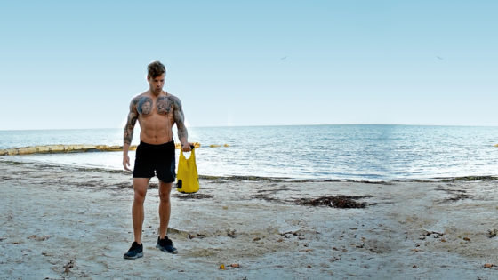 portable kettle bell workout. Man hold a drybell on a beach with his left arm