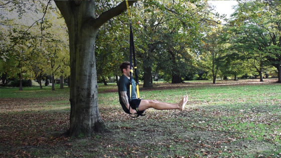 TRX exercise for abs. Man performs a L-sit with a TRX