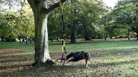 TRX chest workout building strength. Man performs one arm TRX chest press