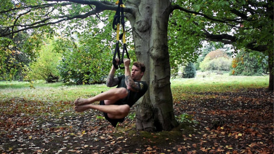 TRX core exercise and workout for home or travel. Man performs TRX core twists in a park