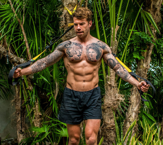 Does running build muscle? Man stands with a TRX in his hand in a jungle