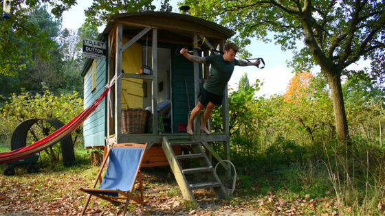 Reduce rounded shoulders with a TRX. Man performs a TRX fly hanging from a gypsy caravan
