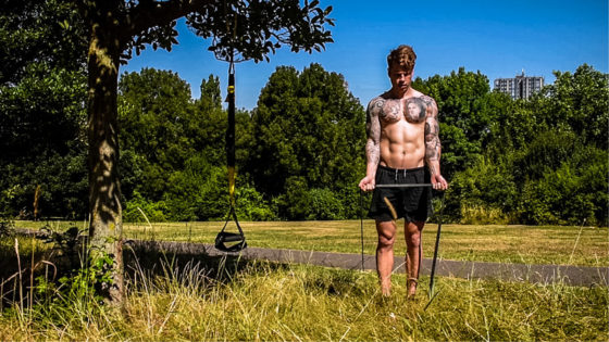 TRX and resistance band workout for arms biceps. Man performs a resistance band bicep curl