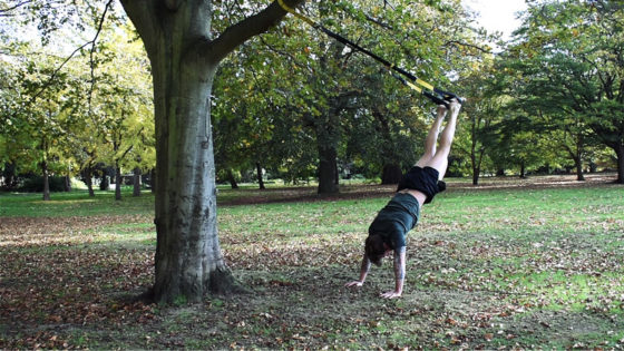 TRX hand stand shoulder workout exercise. Man performs a TRX hand stand press