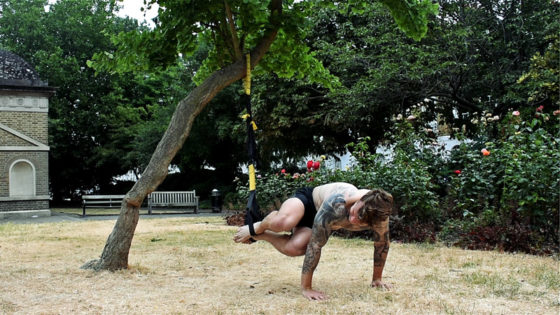 TRX exercise for building abs and getting lean. Man performs TRX twists in a park
