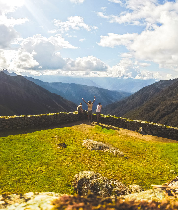 Trekking the Inca Trail to Machu Pichu. Three men standing in the ruins of an Incan City on the 2nd day of the trek looking out onto The Andes mountains