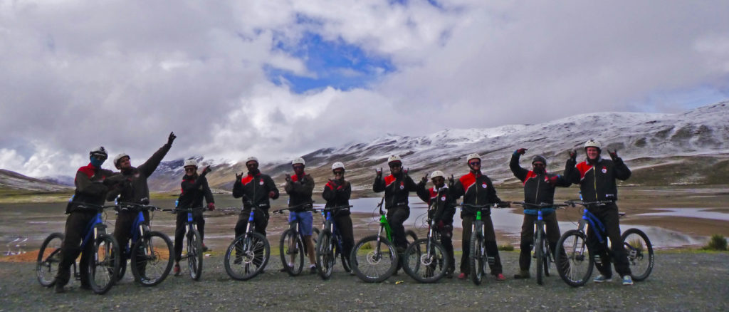 Advice on what to prepare for backpacking La Paz. A group of cyclists waving to camera at the beginning of death road