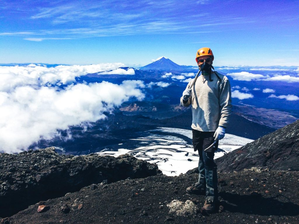 Why you cannot skip Pucon when travelling.  A man standing at the top of Volcan Villarica with Pucon and other volcanoes in the backdrop. A must do hike in Pucon