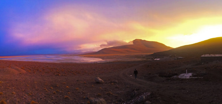 Here's the magic of backpacking San Pedro de Atacama. A view of a lagoon out in the desert with the purple evening sky