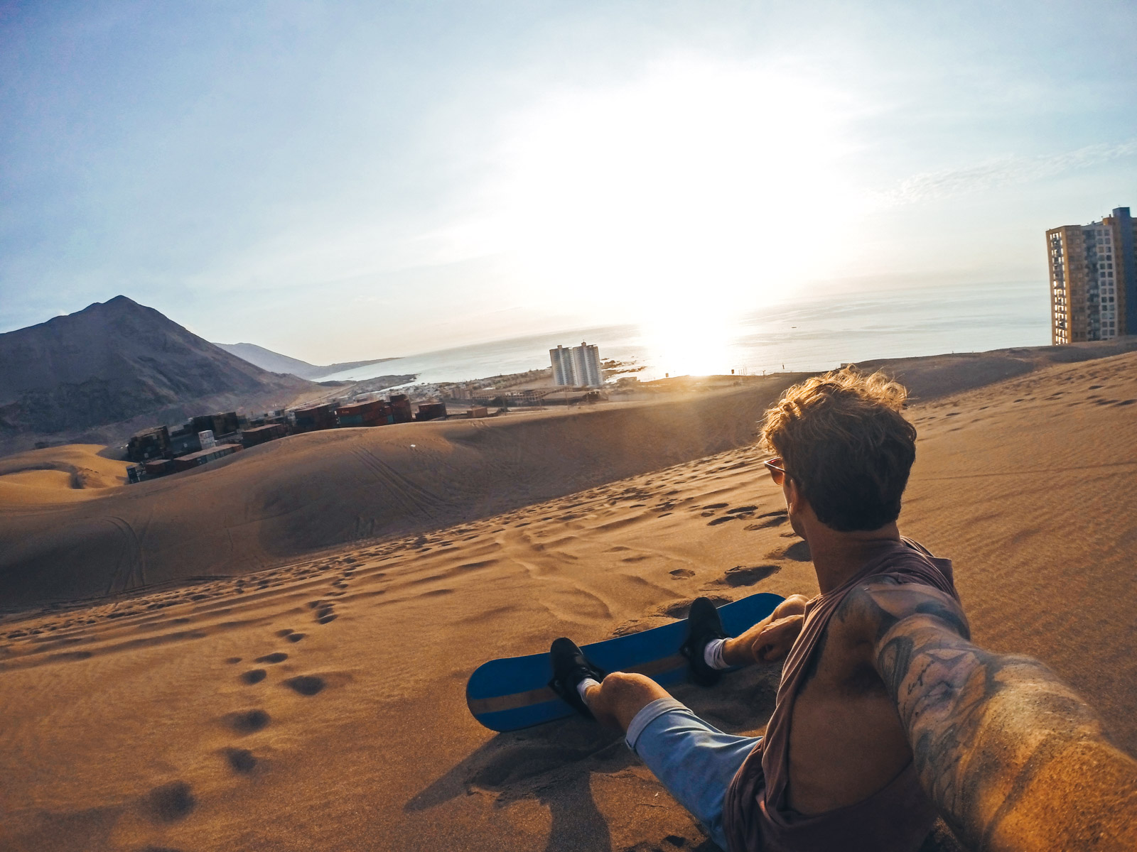 All you need to know for backpacking Iquique. Sand boarding the dunes of Iquique looking over the city. A must do in a group