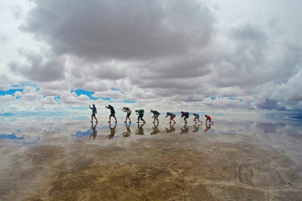 Backpacking the Salt Flats? Here's some useful tips. Nine people creating a photo of 'evolution' on the salt flats with a reflection in the water