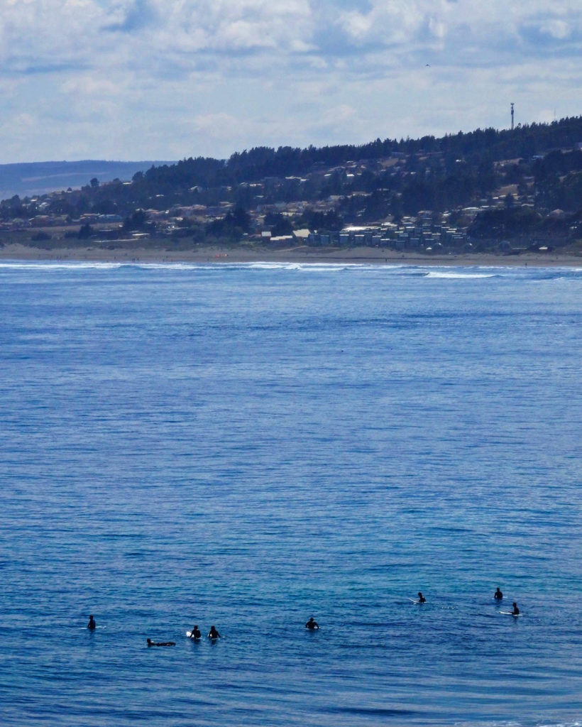 Pichilemu in Chile is a hidden gem to travel. Surfers sit on the water waiting for the next big wave