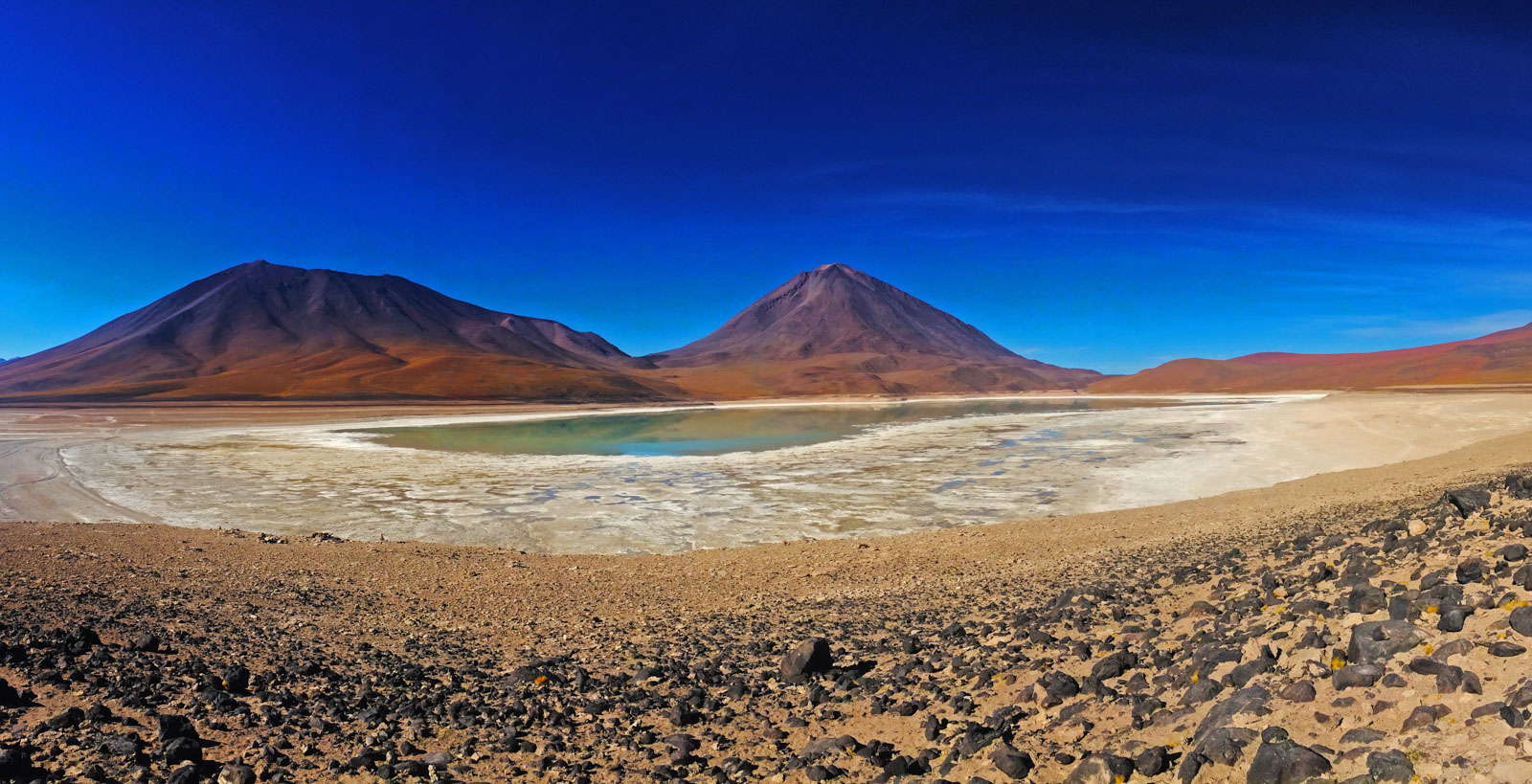 Backpacking the Salt Flats? Here's some useful tips. One of the many lagoons with Flamingos resting in them and pink coloured mountains behind