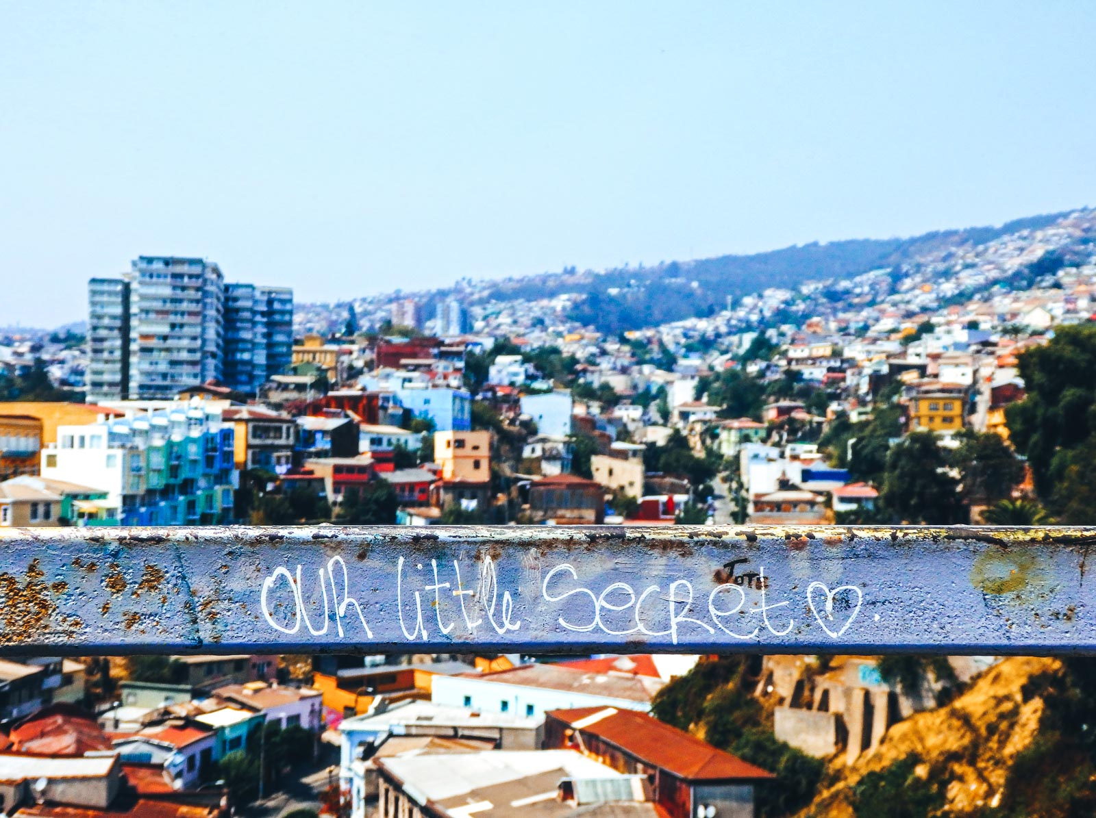 "Travelling Valparaiso? There's no place like it. The view from the top looking over the city of Valparaiso whilst on the free walking tour. The words ""our little secret"" are written on a bar in front"